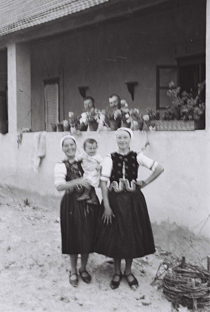 Tornác előtt álló kisgyermeket tartó lányok. (Arany Adalbert László zobor vidéki néprajzi fotói az 1940-es évekből. Lipcsey Gyula hagyatéka.)