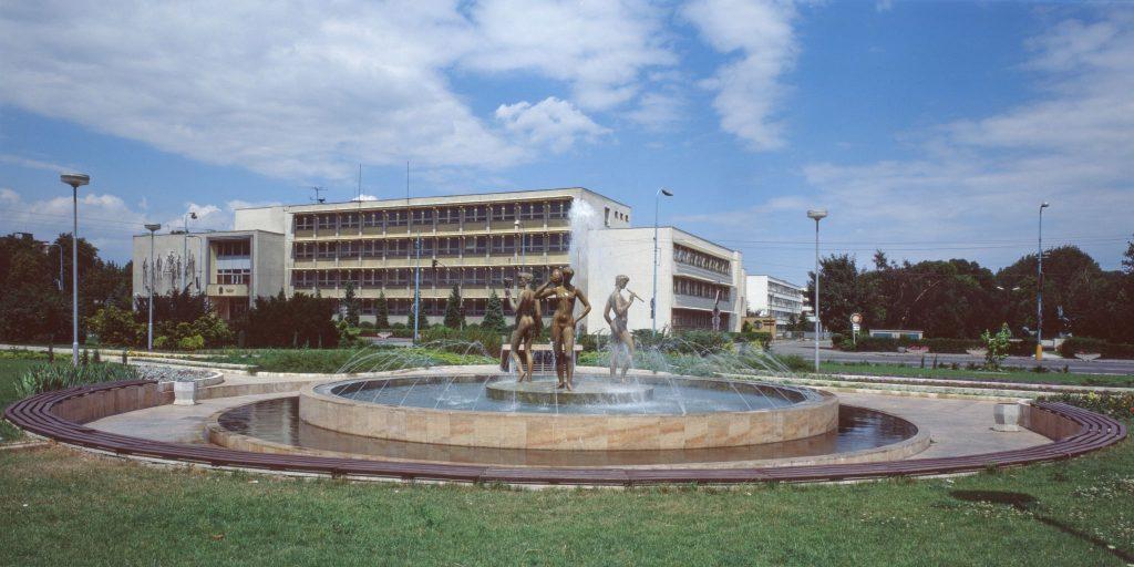 Tündér Ilona szökőkútja, héttérben a Járási Nemzeti Bizottság (